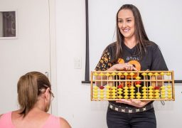 Educadora da Franquia SUPERA ensina aluna a fazer cálculos no ábaco, principal ferramenta do curso de ginástica para o cérebro