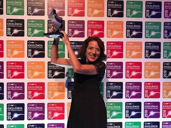Liliana Aragon, Vice-Presidente do SUPERA, recebe troféu da ABF, comemorando estar entre as melhores franquias premiadas do Brasil